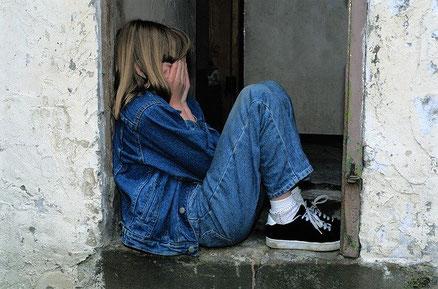 Mädchen sitzt verunsichert und traurig in einem Fenster