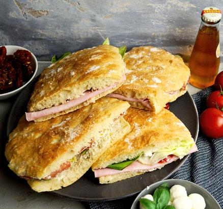 frisch gebackene Ciabatta, mit feinen italienischen Zutaten gefüllt und platt gepreßt, werden zu Pan Bagna