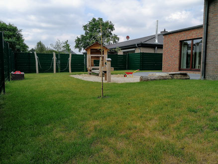 Blick auf einen Teil des Außenbereichs der Kita mit Rasenfläche, Sandkasten und Spielhaus.