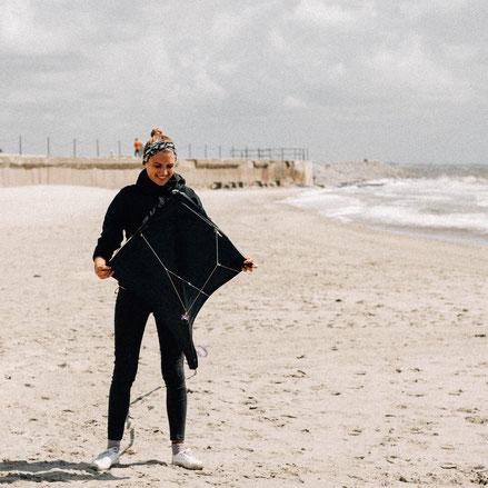 Luisa aus dem Team SALZWASSER lässt am Strand von Norderney einen Drachen steigen.
