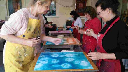 6 vrouwen schilderen twee aan twee op een nat stuk papier. Er zit al aquarelverf op en nu voegen ze nog iets toe om extra patronen te maken. De linker vrouw draagt een gele schort, de driee vrouwen aan de recter kant hebben allemaal een rode schort aan.