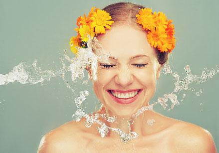 Lachende Frau mit Blumen im Haar und Wasser von der Seite
