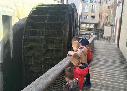 Kinder bestaunen altes Wasserrad