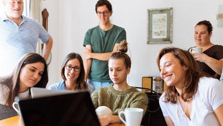 Junge Mädchen sitzen an einem Tisch in einem Seminarraum und schauen gemeinsam in einen Laptop. Im Hintergrund stehen zwei Männer. Sie diskutieren über die Seminarversicherung der ERGO.