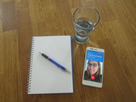 Foto mit Notizblock, Handy und einem Glas Wasser