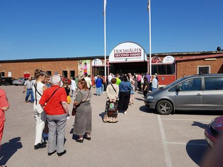 Menschen stehen Schlange vor der Öffnung von Erikshjälpen