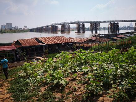 Vue du pont métallique qui enjambe le Tonlé Sap pour relier Phnom Penh à Chrui Changvar, et de quelques maisons flottantes.