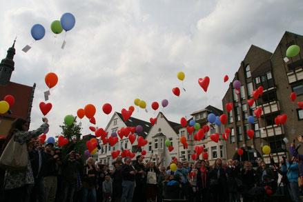 Ein Zeichen gegen die Diskriminierung Homosexueller setzten am Sonntag rund 120 Teilnehmer beim RainbowFlash. Bunte Ballons stiegen gen Himmel. Bild: Reckeweg