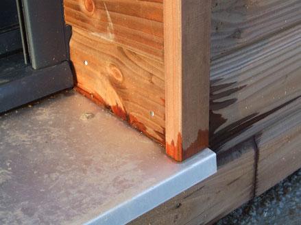 détail d'un pied de tapée de porte-fenêtre : conception piégeante ; le bois retient l'eau et risque de pourrir à terme.