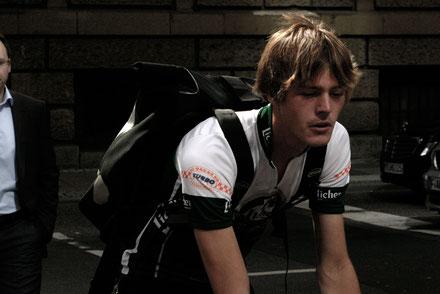 Konzentrierter Radkurier in Frankfurt mit glänzenden Haaren