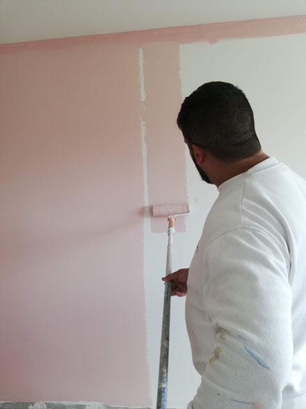 en esta foto estamos pintado una pared de color rosa