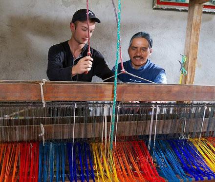 Ein Freiwilligendienstler lernt in einer Weberei das Weben von bunten Baumwollfäden.