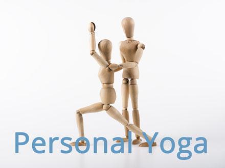 Zwei Holzpuppen stellen dar, wie ein Yoga-Schüler beim Personal Yoga vom Yoga-Lehrer in einer Übung korrigiert wird. Bild C. Schuessler/Fotolia
