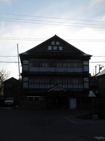 駅の向かいにある旧旅館、富田屋。木造3階建てだ。
