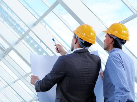 Zwei Architekten mit Plänen bei der Bauleitung
