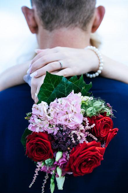 Braut umarmt Bräutigam mit Brautstrauß