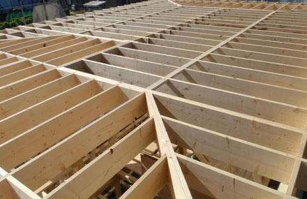 木造軸組工法の屋根の垂木の様子。新築住宅の屋根材が貼られる前の屋根の等間隔に組まれている垂木が明るく日差しを浴びています。