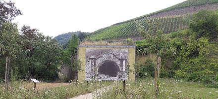 Einer der Tunneleingänge der nicht vollendeten Bahnlinie. Die Tunnelanlage wurde dann für den Bau des Regierungsbunker in Ahrweiler verwendet. Die Eingänge sind heute zubetoniert und mit einer Fotoleinwand historisch nachempfunden.