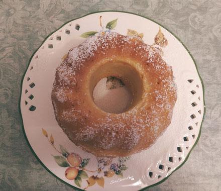 Ciambellone ricotta e limone con zucchero a velo servito su un piatto da portata