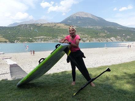 dame de 67 ans au bord du lac de Serre-Ponçon, avec planche à voile et windfoil aeromod