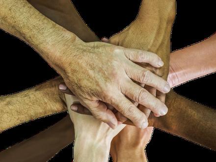 Verschiedene Menschen haben ihre Hände zusammengelegt und symbolisieren Zusanmenhalt.