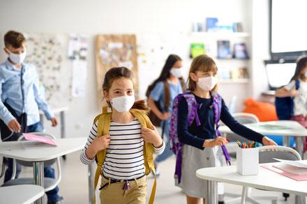 Schüler mit Masken im Klassenzimmer
