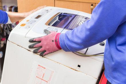 壊れた洗濯機を運ぶ業者