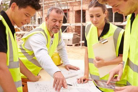 Architekten und Bauleiter besprechen Baupläne auf Baustelle