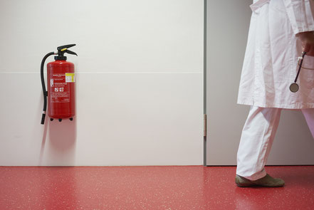 Arzt in Krankenhausflur mit Feuerlöscher an der Wand