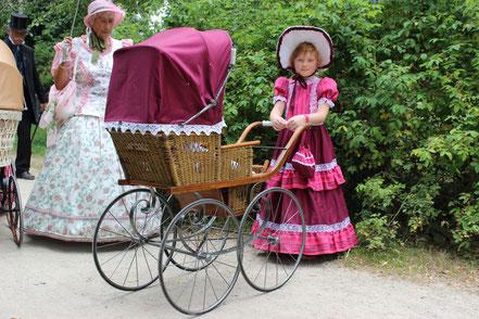Mädchen mit historischen Kinderwagen