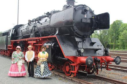 Biedermeier vor einer großen Dampflokomotive