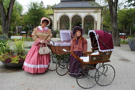 Biedermeierfrauen mit Kinderwagen