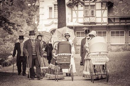 Biedermeiergruppe flaniert im Park