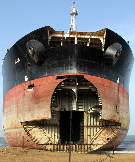 Petrolier encallat a la platja a mig desballestament, mireu la mida de les persones comparades amb el vaixell amb cara de monstre marí.