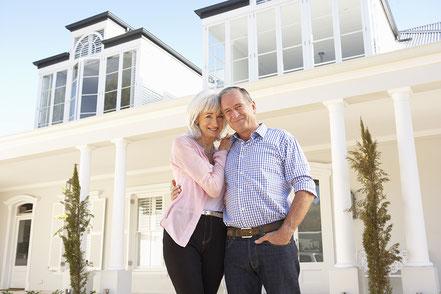 Zufriedenes Paar vor Ihrer Villa in Hamburg mit Hauspersonal
