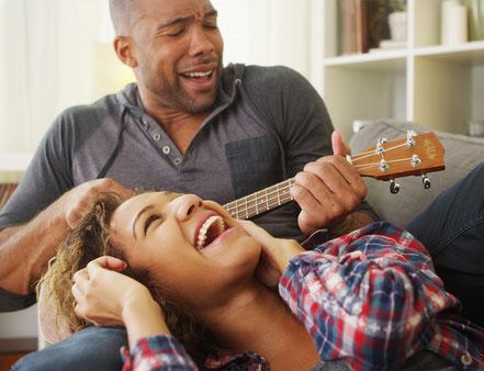 Mann spielt scherzhaft Ukulele und bringt seine Frau zum Lachen