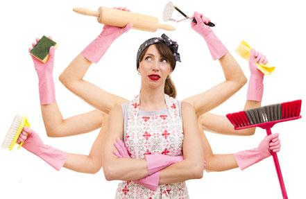 Genervte Hausfrau hält Putzutensilien einer Haushaltshilfe in vielen Armen