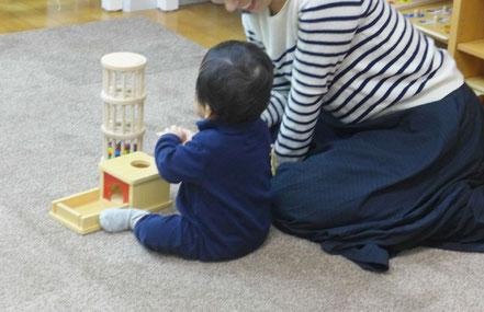 幼児教室のピッコロコース(0歳児)のモンテッソーリの活動で、10ヶ月の幼児が手でモノを確かめています。