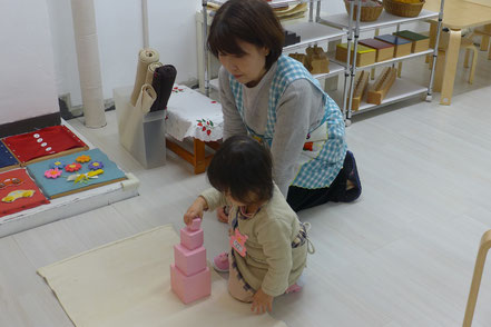 幼児教室ステッラコース(1歳児)のモンテッソーリ活動で、先生の援助をうけながら、ピンクタワーのおしごとに取り組んでいます。
