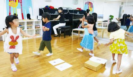 幼稚園児がリトミックで、二分音符と4分音符を組み合わせてできたリズムに合わせてステップをふんでいます。