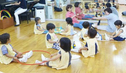 母子分離クラスの2歳児が、ペアになって、フープを使ったリトミックを行っています。