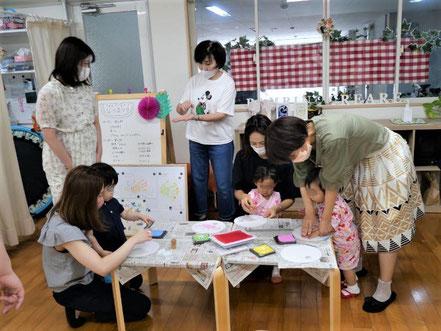 幼児教室の夏祭りで未就園児が自分だけのうちわを製作。好きな色を選んで手形をうちわに押しています。
