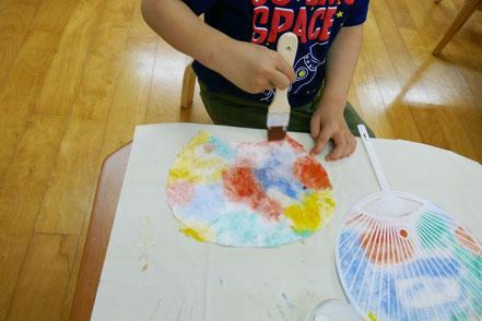 うちわの骨組みに和紙を貼るために、はけを使って和紙にのりをまんべんなく塗っています。