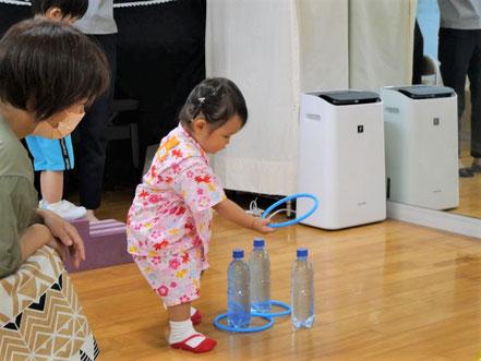 幼児教室の夏祭りで1歳児が輪投げを楽しんでいます。