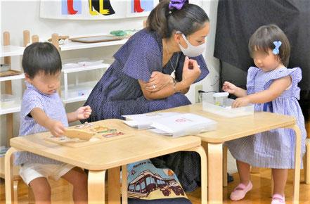 モンテッソーリの活動で、1歳児がそれぞれパズルとビー玉押しに集中して活動しています。