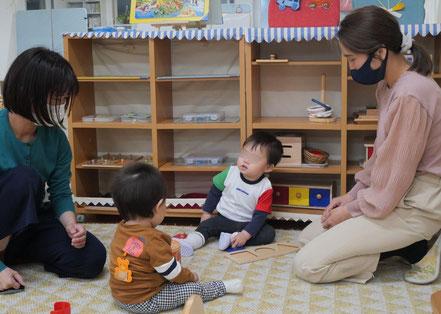 0歳児がモンテッソーリの個別活動でお座りをして手指の活動を楽しんでいま。