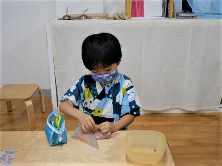 幼児教室の夏祭りで幼稚園児が針金と折り紙を使って風車を作っています