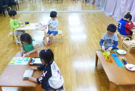 幼児教室の幼稚園児クラスの生徒が、新教室でモンテッソーリ活動に集中して取り組んでいます。