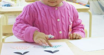 幼児教室のモンテッソーリ活動で、折り紙を使ったおひな様づくりを、1歳児の生徒が行っています。