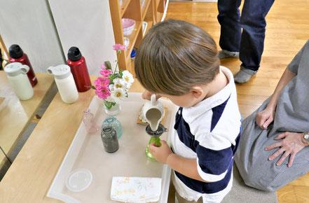モンテッソーリ活動の生け花の活動で、1歳児がじょうごを使って花びんに水をこばさないように注いでいます。